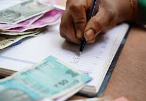 man writing down accounts money in his book