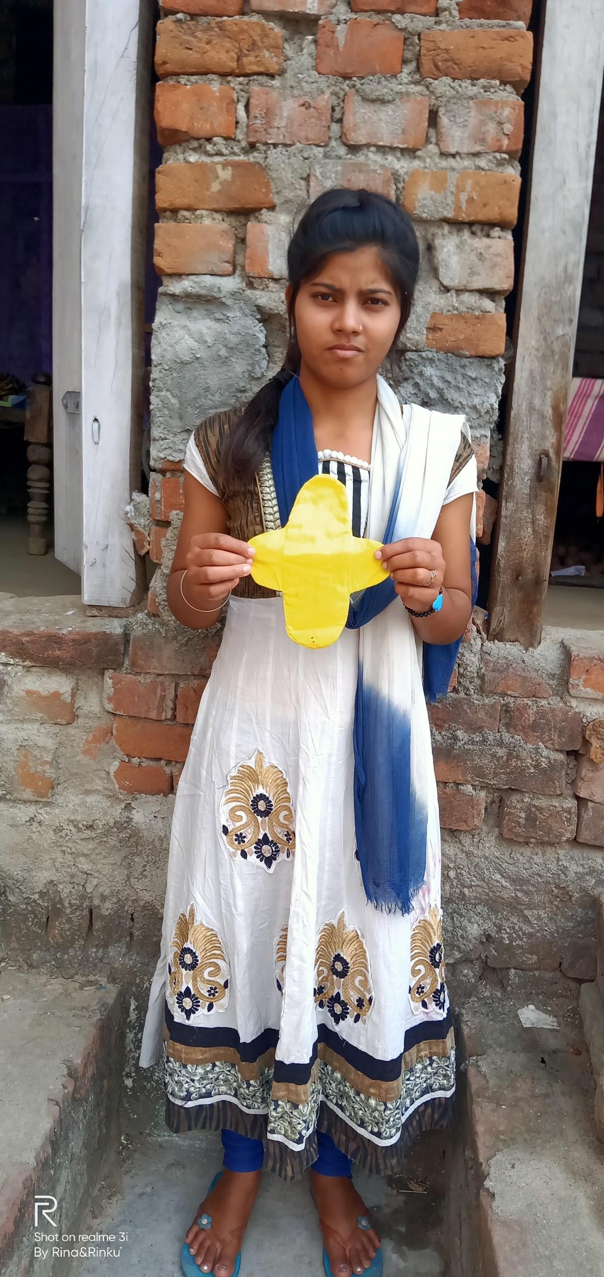 Nitu Kumari holding a hand-sewn pad