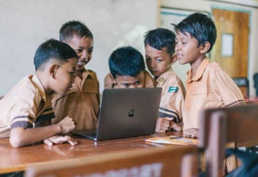 a group of school kids reading from a single computer