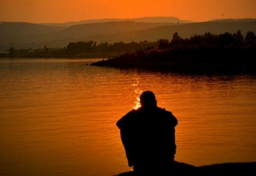 man sitting at a hill top during sunset