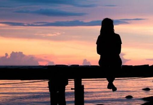 woman sitting on a bridge alone and watching sunset