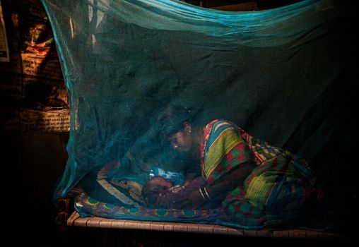 mother and baby sleeping under mosquito net