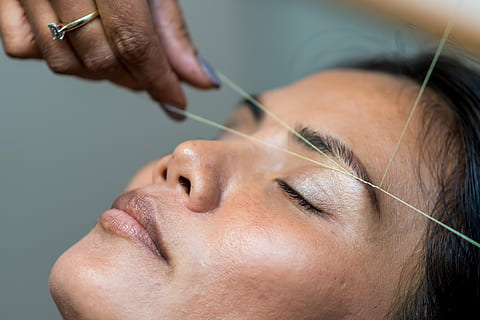 woman getting her eyebrows threaded