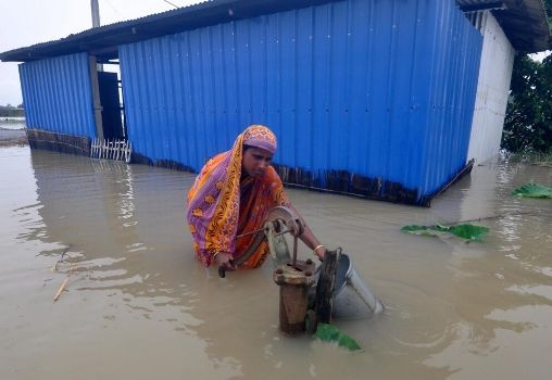 assam 2020 floods woman walks in waist-high water