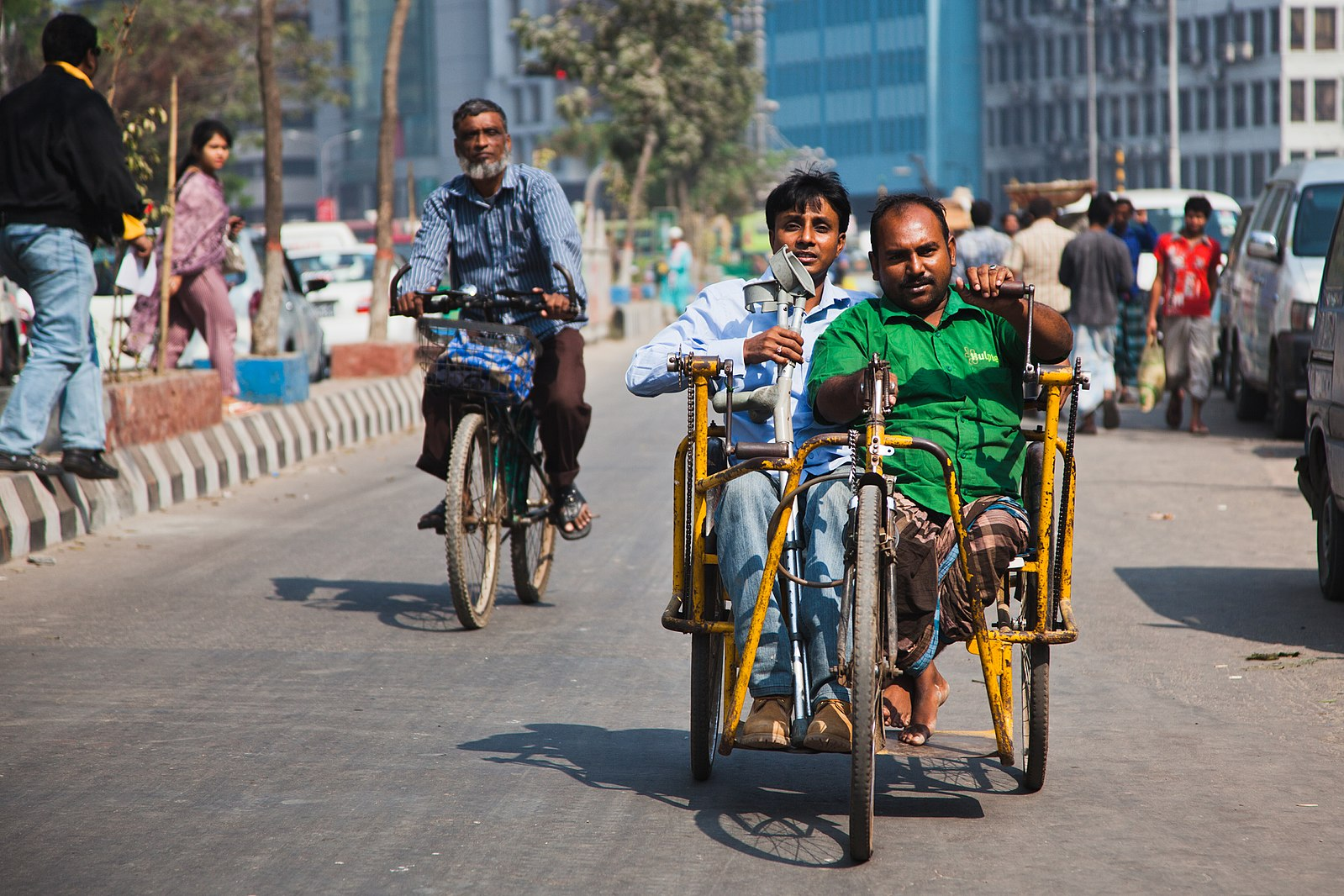 Two person with disability riding a tricycle