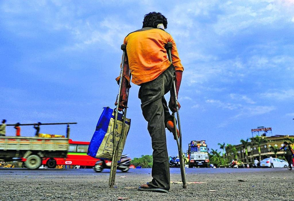 A person left stranded on a crutch on a road with his back visible