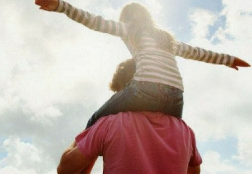 daughter sitting on father's shoulders