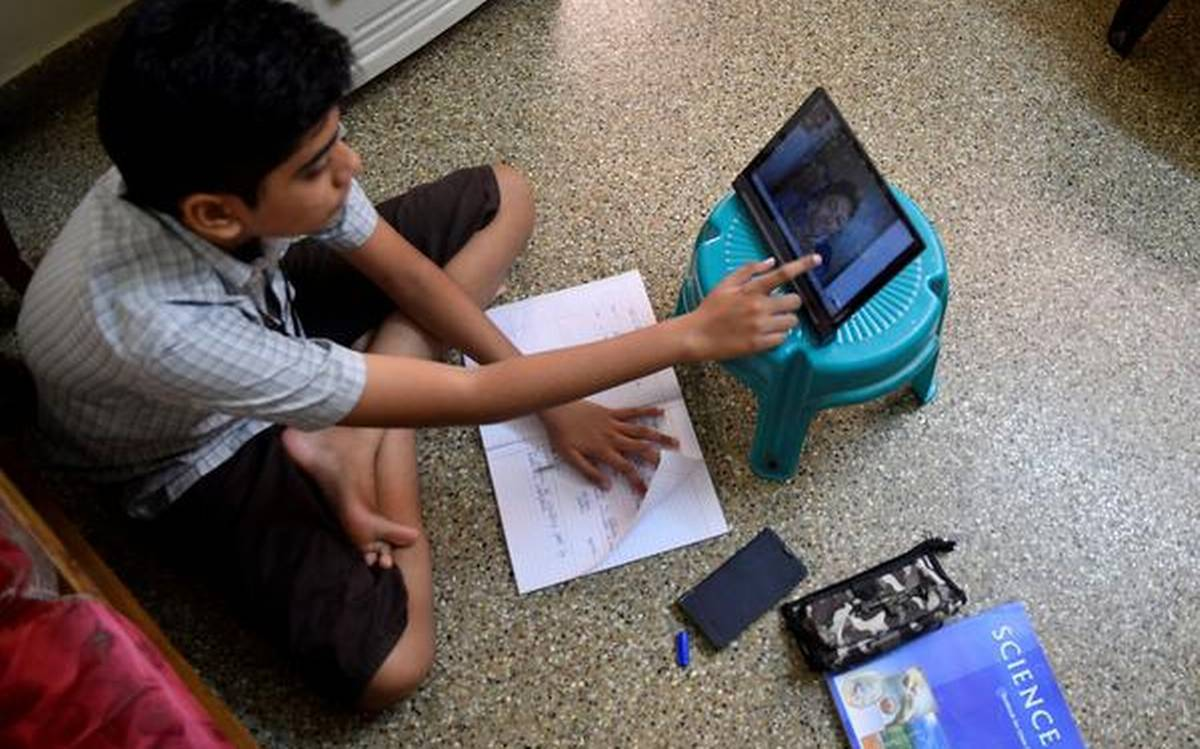 Image of a child using a tablet to study, while studying from a notebook