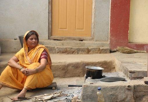 A woman is sitting in a rural setup near a chulah.
