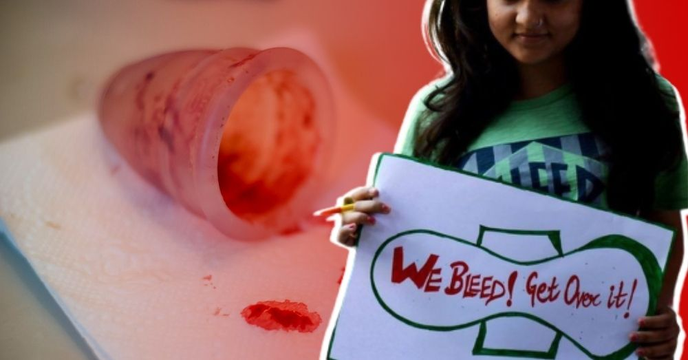 A girl holding a poster that says 'we bleed! get over it!' in the backdrop of a bloody menstrual cup