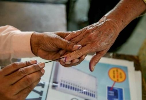 an old person's hand being inked after voting
