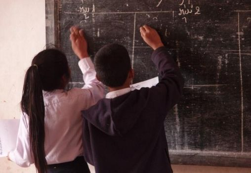 a girl and boy in school uniform writing on the blackboard in the classroom