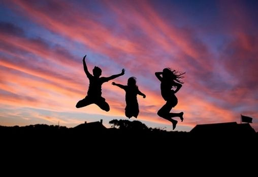 silhouette of three people jumping in the air