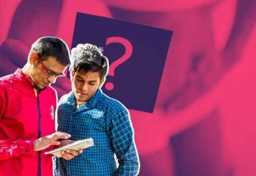 Men looking at a phone with a girl holding a question mark in the background