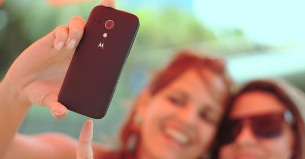 two women clicking a selfie with their phone