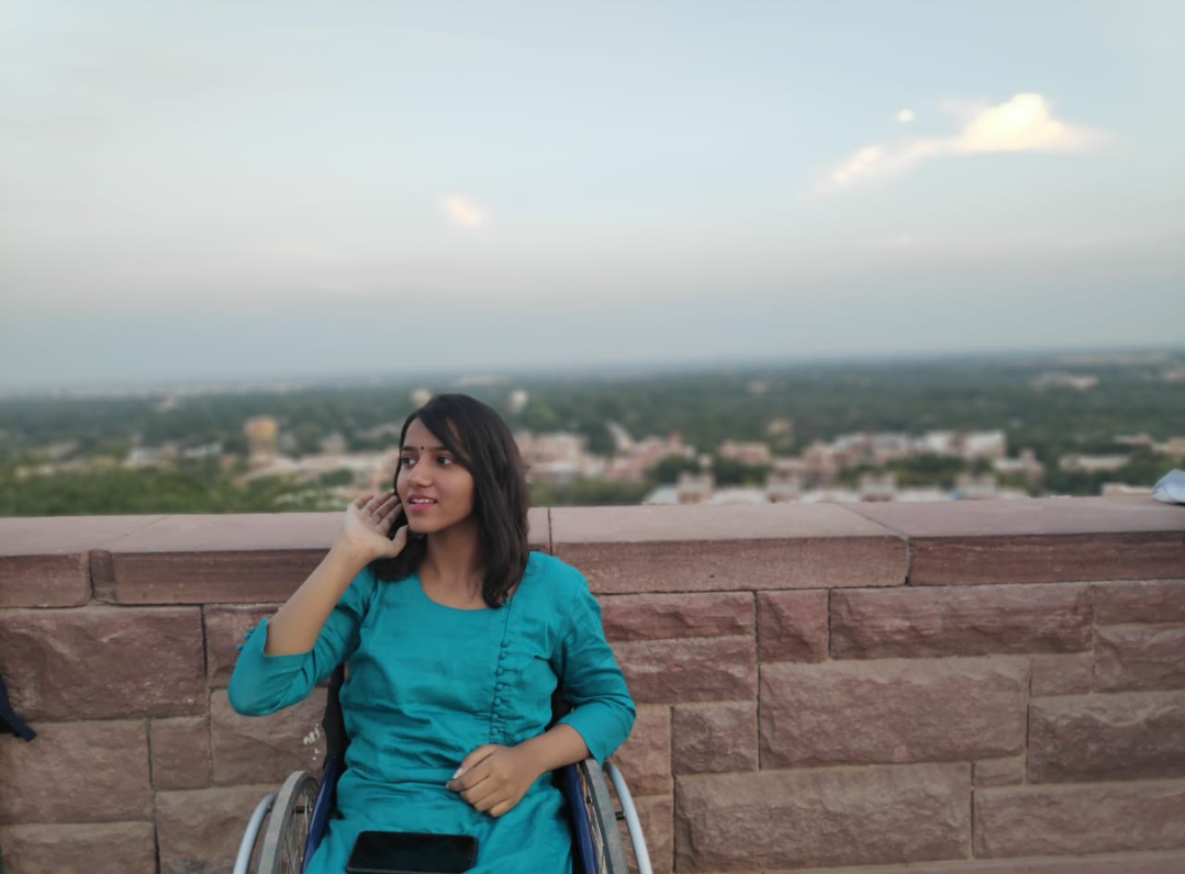 Its a photograph of srishti, sitting on her wheelchair. She is wearing a blue colored Kurti. She is looking towards her right.There is a wall in the background.