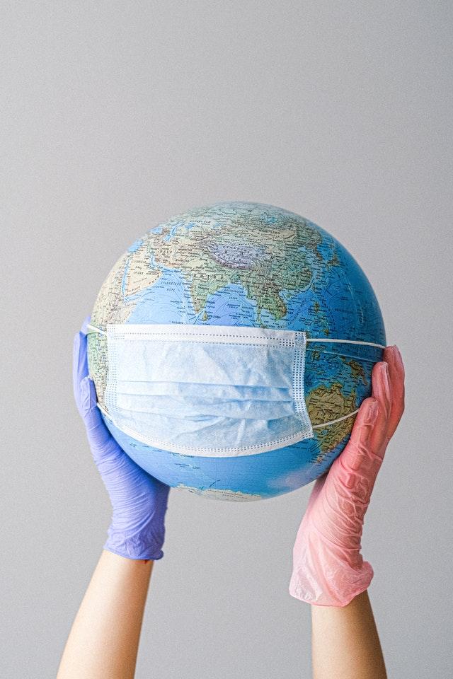 latex gloves holding globe