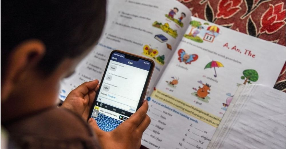 Image of a child looking into a phone screen, trying to use educational software, with school books in the background.