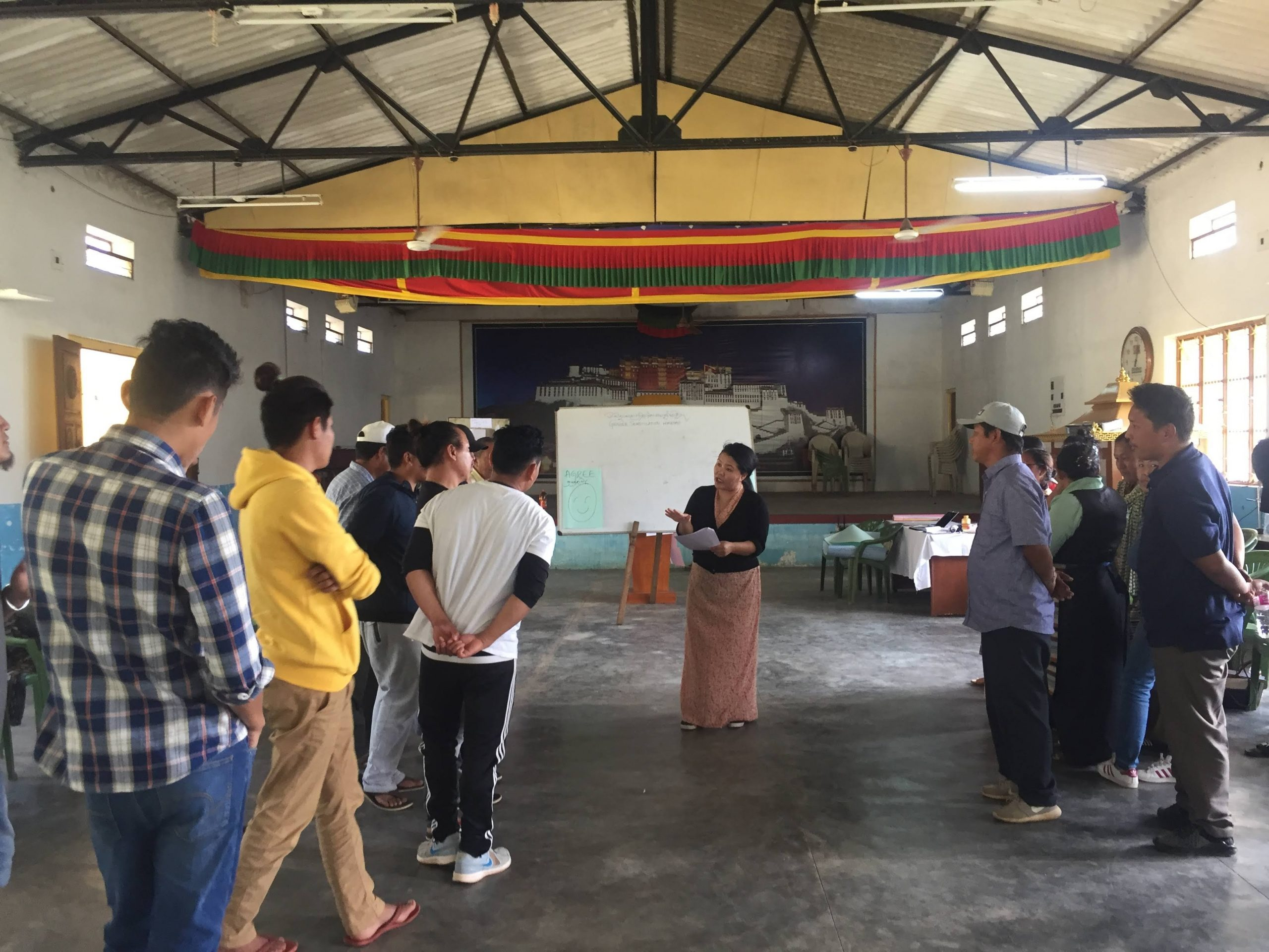 Tsering Kyi leading a gender education session with men of the Tibetan community.