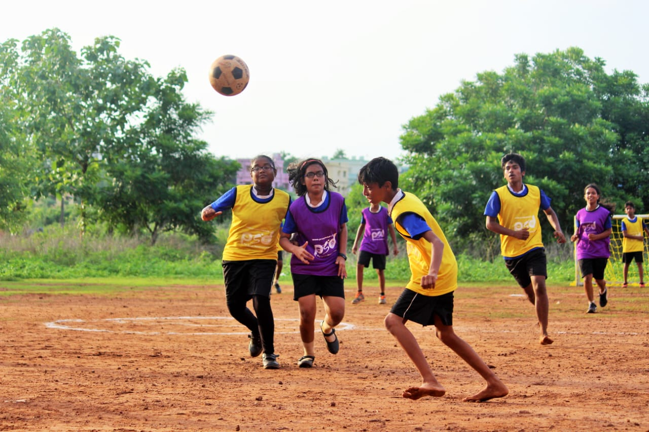 1 girl and two boys playing soccer on a dirt field