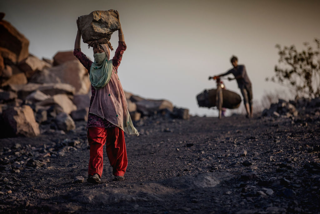 A female worker has piled coal on her head while she is