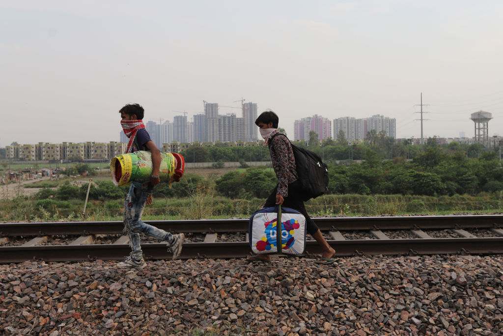 Migrant workers carrying their belongings walk along a