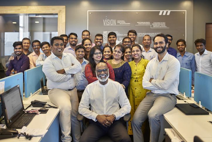 Proud Indian CEO Posing with Smiling Company Staff in Office