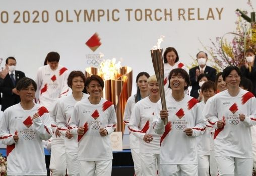 image of a women's team taking torch for relay for okyo 2020 olympics