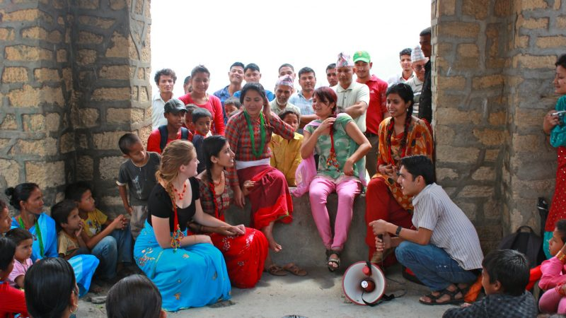 A group of street theatre actors discussing the practice of 'chhaupadi' as onlookers listen.