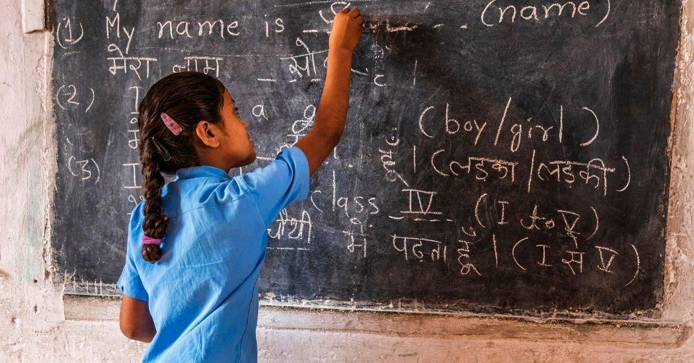 a young girl writing on a blackboard in india