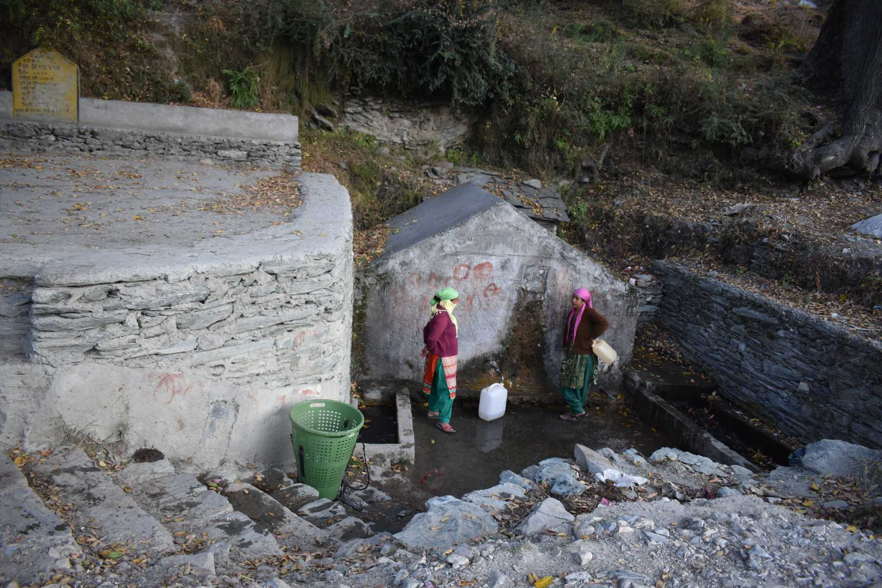 women collecting water from spring
