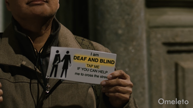 A person holding a card that says I am deaf and blind. Tap me if you can help me cross the street.