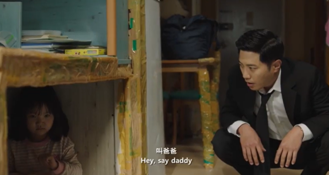 A man perched down calling to a young girl hidden under the table. The caption reads Hey, say daddy.