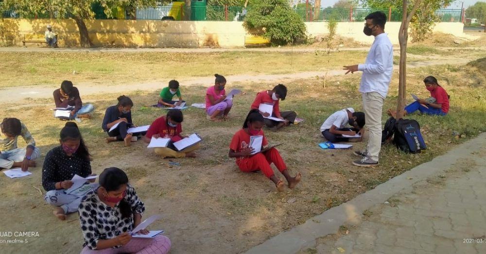 पढ़ाई करते झुग्गियों में रहने वाले बच्चे।