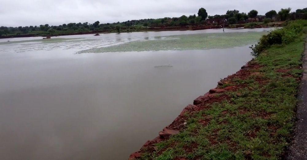 पानी से लबालब भरा हुआ तालाब, जिसके कभी भी टूटने की सम्भावना है।
