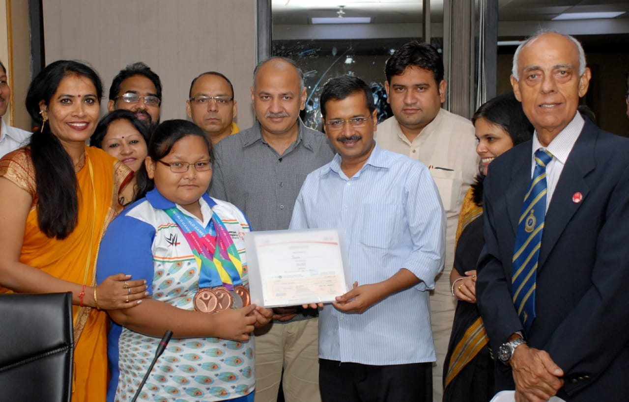Pushpa Kadayat wearing 4 medals= 3 bronze and 1 silver around her neck being felicitated by the chief minister of Delhi Arvind Kejriwal and is surrounded by supporters.